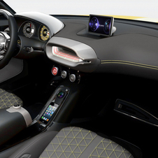 The interior is minimalist with black leather seats with yellow accents.